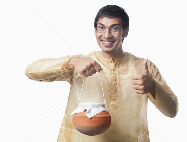 Bengali man carrying a pot of rasgulla and showing thumbs up sig Stock photo © imagedb