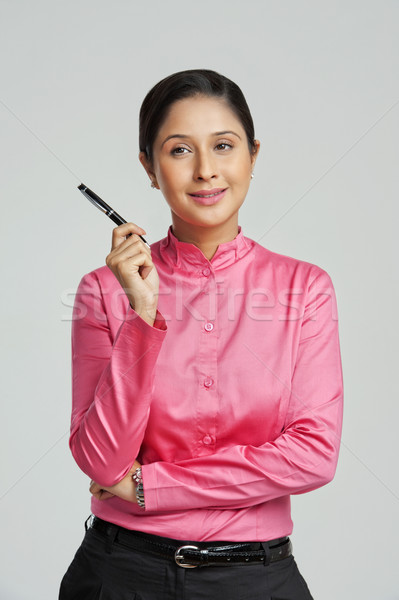 Businesswoman holding a pen and smiling Stock photo © imagedb