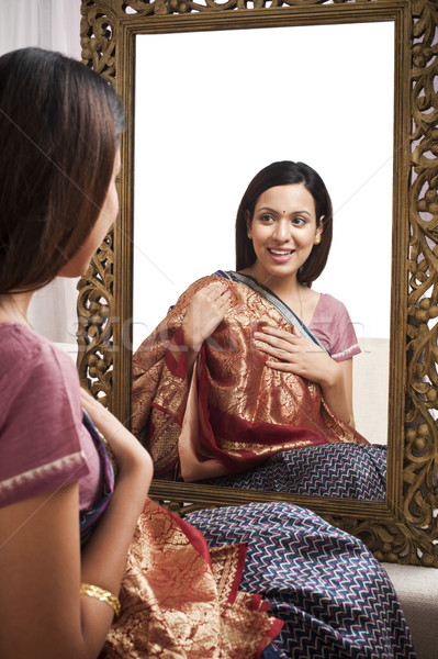 Reflection of a woman in mirror trying a sari on herself Stock photo © imagedb