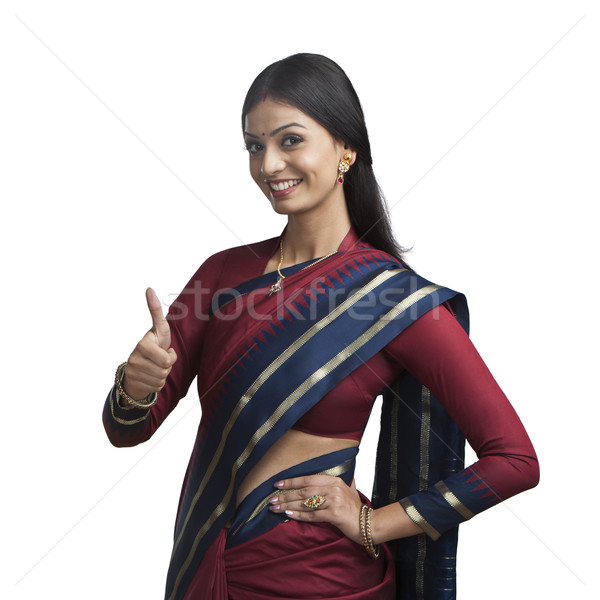 Traditionally Indian woman gesturing thumbs up sign Stock photo © imagedb