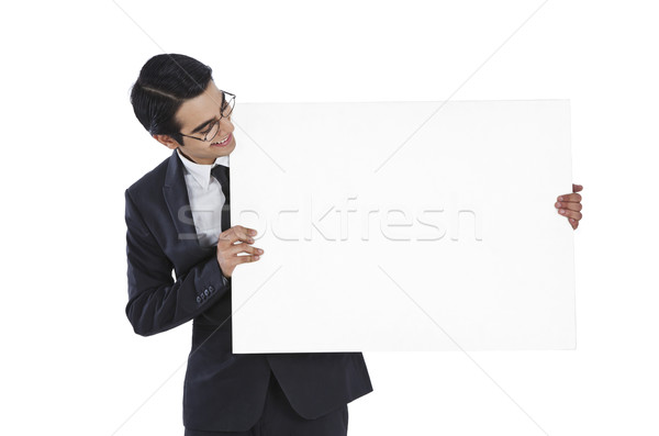 Businessman showing a blank placard and smiling Stock photo © imagedb