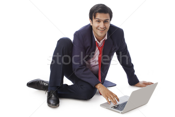 Businessman working on a laptop and smiling Stock photo © imagedb