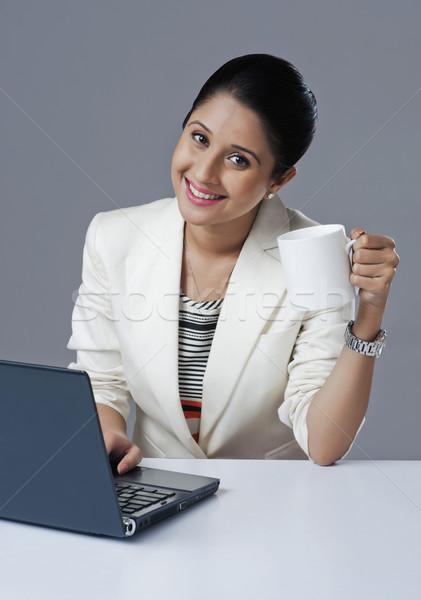 Işkadını kahve kupa dizüstü bilgisayar kullanıyorsanız iş kadın Stok fotoğraf © imagedb
