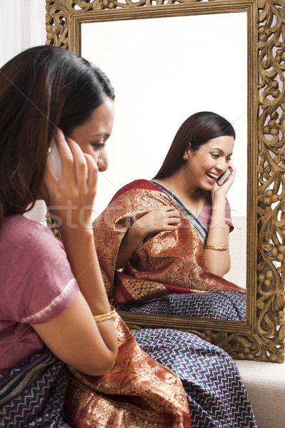 Reflection of a woman in mirror trying a sari on herself and talking on a mobile phone Stock photo © imagedb