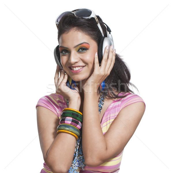 Beautiful young woman listening to music on headphones Stock photo © imagedb