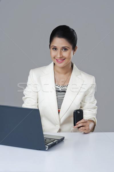 деловая женщина используя ноутбук мобильного телефона служба бизнеса Сток-фото © imagedb
