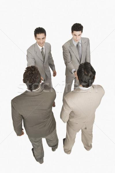 Négy üzletemberek kézfogás üzletember mosolyog boldogság Stock fotó © imagedb