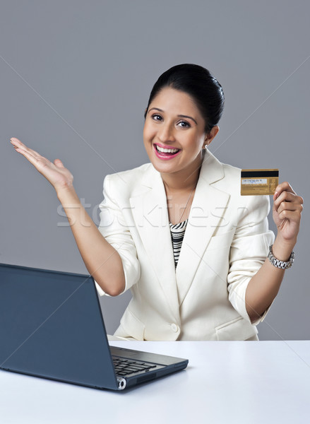 Businesswoman looking excited while doing online shopping with a laptop Stock photo © imagedb