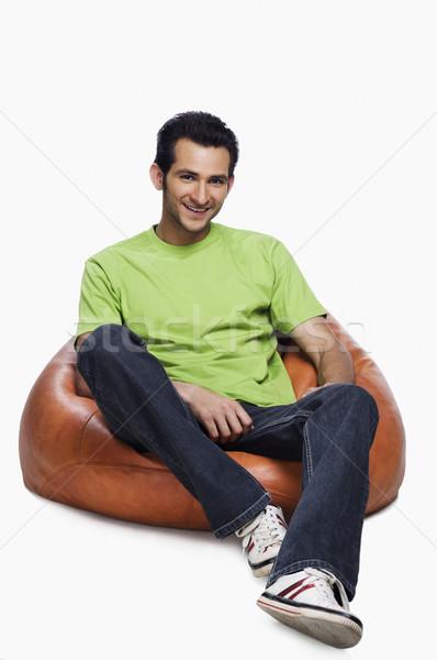 Retrato homem sessão saco de feijão sorridente verde Foto stock © imagedb