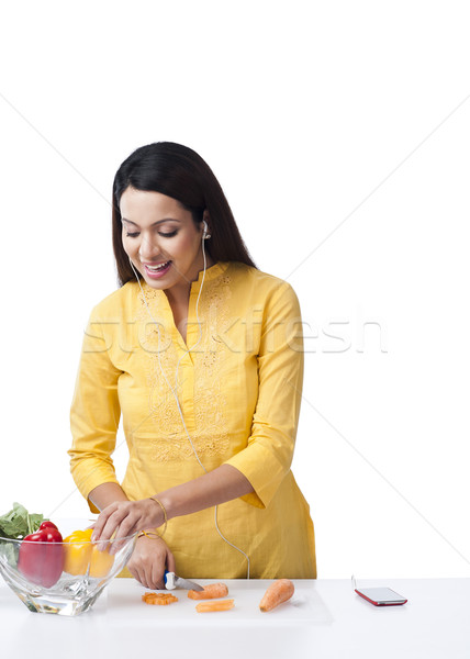 Woman cutting vegetables and listening music with an mp3 player Stock photo © imagedb