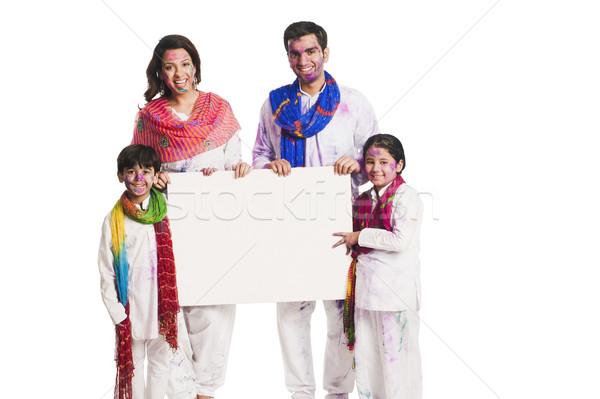 Family celebrating Holi and holding a blank placard Stock photo © imagedb