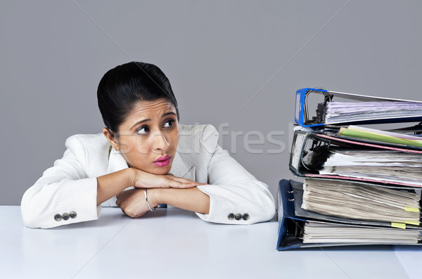 Businesswoman looking at piles of files in an office Stock photo © imagedb