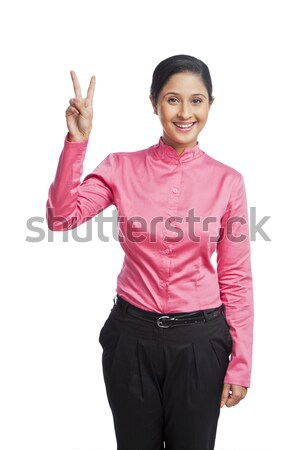 Portrait of a businesswoman gesturing victory sign Stock photo © imagedb