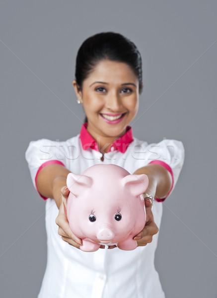 Portrait of a woman holding a piggy bank Stock photo © imagedb