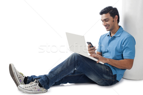 Mann mit Laptop Handy Internet Wand Stock foto © imagedb