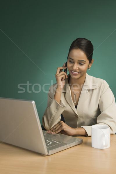Imprenditrice utilizzando il computer portatile parlando cellulare donna sorriso Foto d'archivio © imagedb