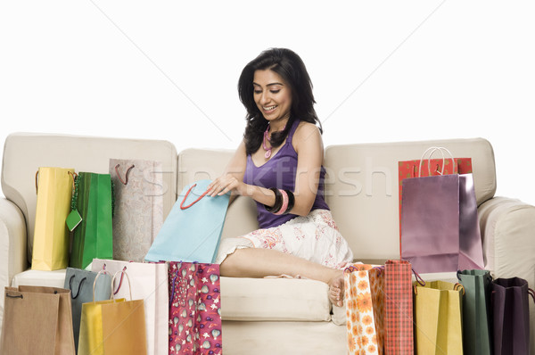 Nő ül kanapé tart bevásárlószatyor boldog Stock fotó © imagedb