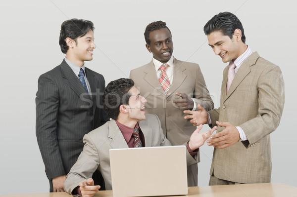 Quattro imprenditori parlando laptop ufficio comunicazione Foto d'archivio © imagedb