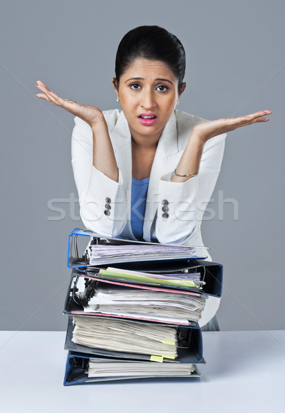 Businesswoman leaning on a stack of files and looking upset Stock photo © imagedb