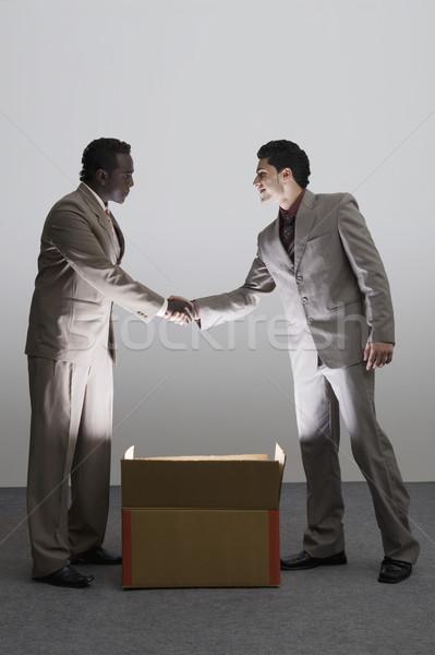 Kettő üzletemberek kézfogás megvilágított kartondoboz üzlet Stock fotó © imagedb