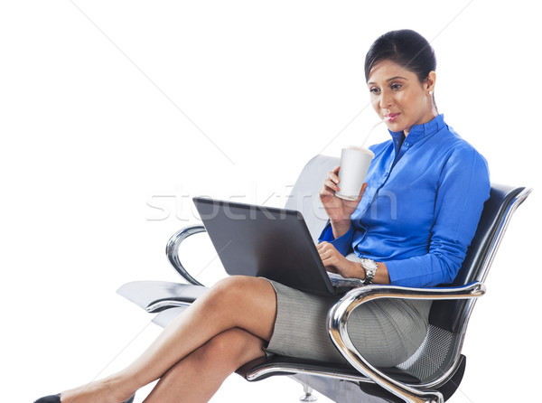 Businesswoman drinking soft drink while using a laptop Stock fotó © imagedb