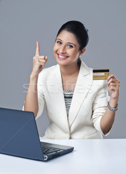 Portrait of a businesswoman holding a credit card and gesturing Stock photo © imagedb