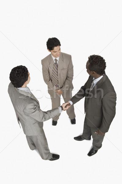 Due imprenditori stringe la mano un altro imprenditore piedi Foto d'archivio © imagedb