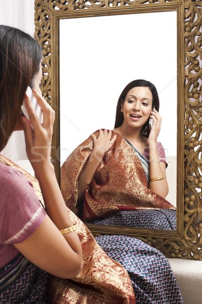 Reflectie vrouw spiegel praten mobiele telefoon mode Stockfoto © imagedb
