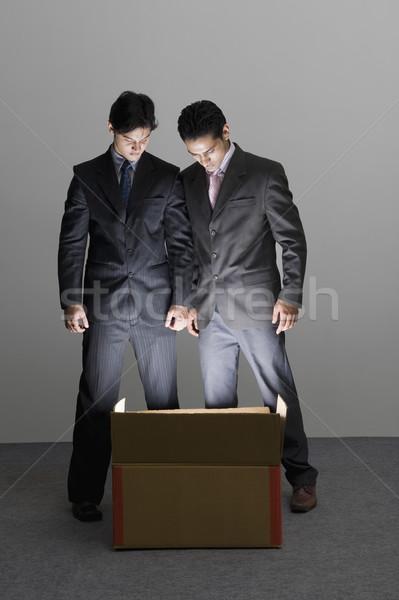 Kettő üzletemberek néz megvilágított kartondoboz üzlet Stock fotó © imagedb