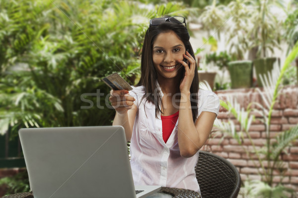 Woman shopping online and talking on a mobile phone Stock photo © imagedb