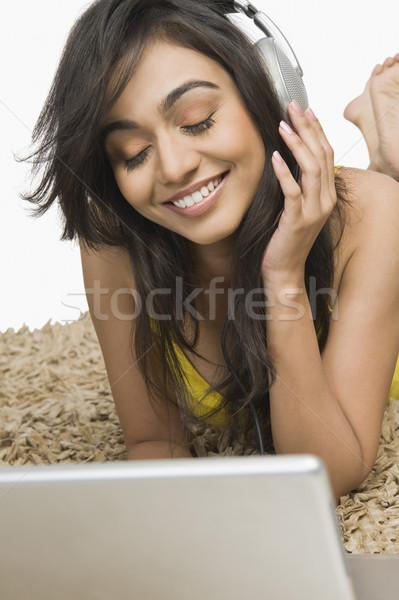 женщину прослушивании наушники улыбаясь ноутбука молодые Сток-фото © imagedb