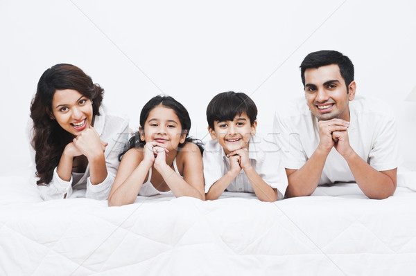 Portrait of a happy family smiling on the bed Stock photo © imagedb
