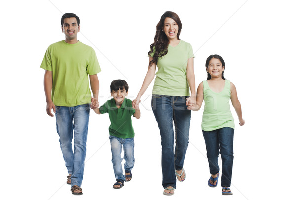 Portrait of a happy family holding hands and walking Stock photo © imagedb