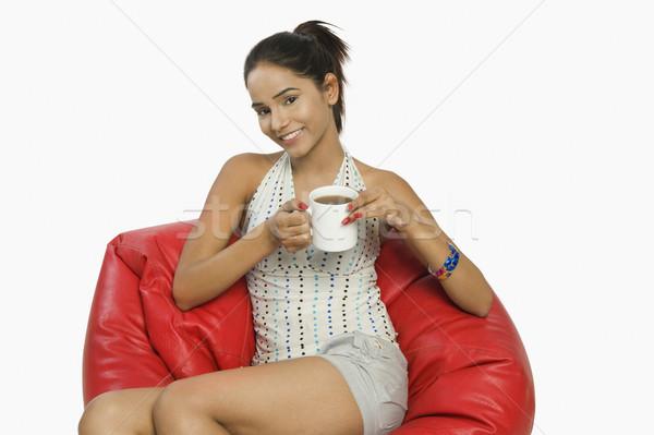Mulher sessão saco de feijão copo café sorrir Foto stock © imagedb