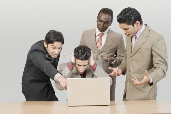 Cztery biznesmenów patrząc laptop działalności Zdjęcia stock © imagedb