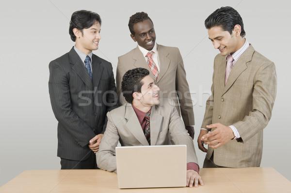Négy üzletemberek beszél laptop üzlet üzletember Stock fotó © imagedb