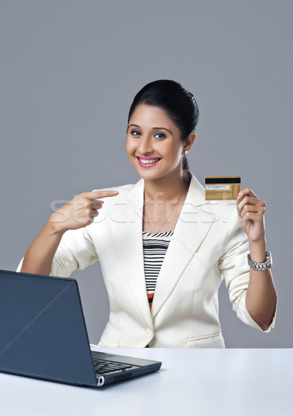 Portrait of a businesswoman pointing towards a credit card Stock photo © imagedb