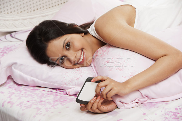 Woman text messaging on a mobile phone on the bed Stock photo © imagedb