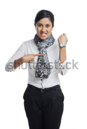 Businesswoman clenching teeth and pointing toward a wristwatch Stock photo © imagedb