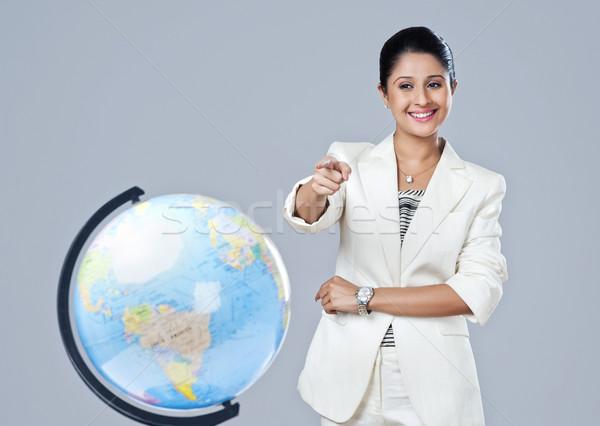 üzletasszony mutat földgömb mosolyog üzlet nő Stock fotó © imagedb