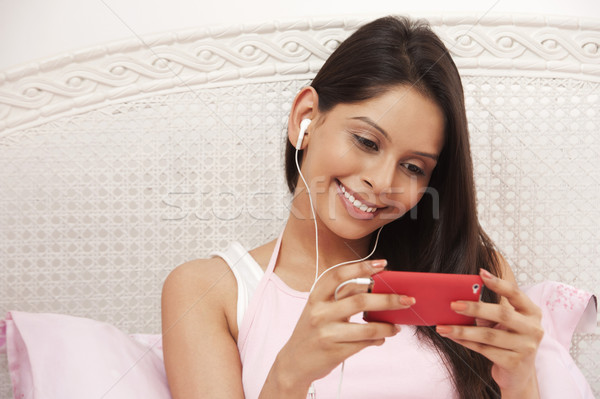Woman listening to music on a mp3 player Stock photo © imagedb