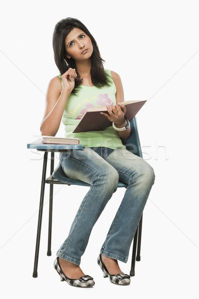 Egyetemi hallgató gondolkodik osztályterem nő könyv toll Stock fotó © imagedb