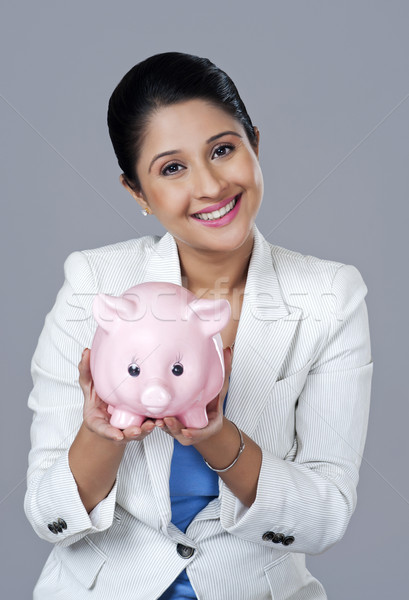 Portrait of a businesswoman holding a piggy bank Stock photo © imagedb