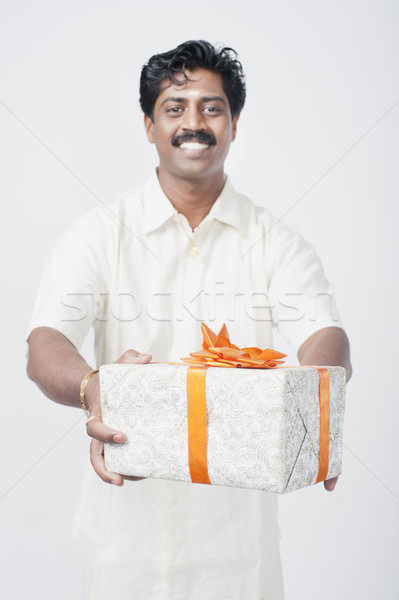 South Indian man giving a gift box Stock photo © imagedb