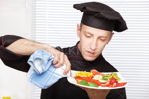 Chef cleaning edge of a fruit plate with cloth Stock photo © imarin