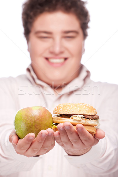 chubby man holding apple and hamburger Stock photo © imarin