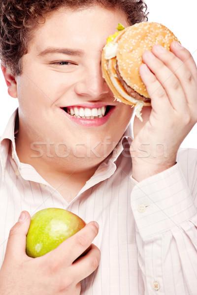 Fiatal pufók férfi tart alma hamburger Stock fotó © imarin