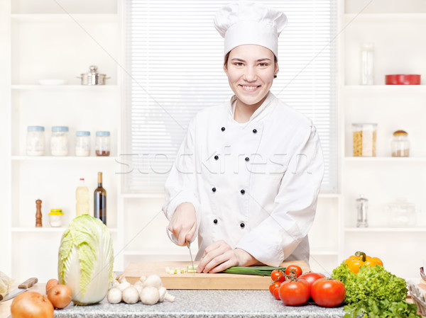 female chef cutting onions on the cutting board in kitchen Stock photo © imarin