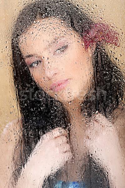 Vrouw achter glas vol waterdruppels mooie vrouw Stockfoto © imarin