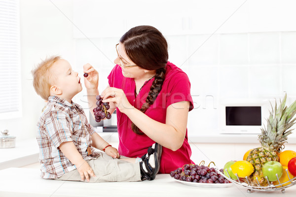 Mother feeding child with grapes Stock photo © imarin